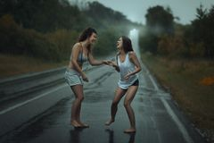 Girls standing in the rain on roadway. Royalty Free Stock Images