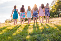 Girls Standing Together Facing the Bright Sunset Royalty Free Stock Photography
