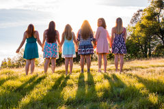Girls Standing Together Facing the Bright Sunset Royalty Free Stock Image
