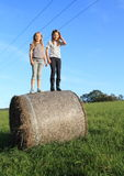 Girls standing up on package of hay Royalty Free Stock Images