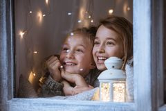 Girls standing beside window Royalty Free Stock Image