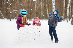 Girls stands behind wall made of snow blocks, boy throws snowball Stock Images