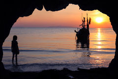 Girls stands in front of the cave by the sea with local fishing boats. royalty free stock images