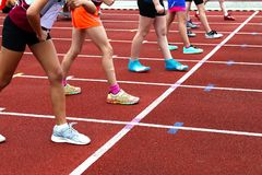 Girls at the start of a race. Young girls at the start of an athletic race on a racetrack royalty free stock photo