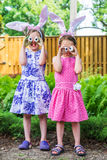 Girls Sticking Out Their Tongues with Silly Egg Eyes. A funny portrait of two girls sticking out their tongue having fun on Easter wearing bunny ears and holding Royalty Free Stock Photos