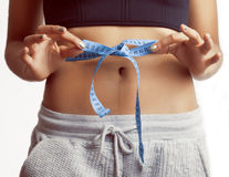Girls stomach measuring with tape twice isolated close up Royalty Free Stock Photo