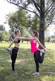 Girls stretching your legs.At park,city. The girls stretch their legs. After each exercise, the muscles should be stretched to prevent injury.n royalty free stock images
