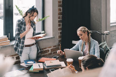 Girls students drinking coffee and studying together at desk. Beautiful girls students drinking coffee and studying together at desk Royalty Free Stock Images
