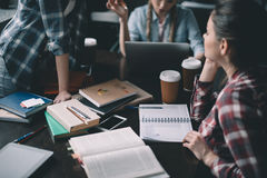 Girls students drinking coffee and studying together at table. Concentrated girls students drinking coffee and studying together at table stock photo