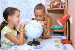 Girls study globe Royalty Free Stock Image