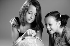 Girls studying globe Stock Photos