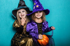 Girls in a suit of a witch. Halloween. Fairy. Tale. Studio portrait on blue background Stock Image