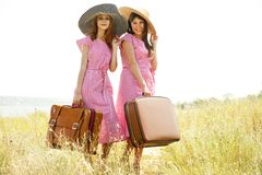 Girls with suitcases at countryside. Stock Photos