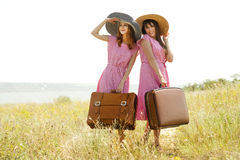 Girls with suitcases at countryside. Royalty Free Stock Photos