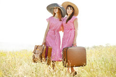 Girls with suitcases at countryside. Royalty Free Stock Photography
