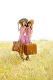 Girls with suitcases at countryside. Royalty Free Stock Photo
