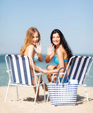 Girls sunbathing on the beach chairs Stock Images