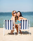 Girls sunbathing on the beach chairs Stock Photos