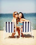 Girls sunbathing on the beach chairs Royalty Free Stock Photos