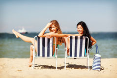 Girls sunbathing on the beach chairs Royalty Free Stock Images