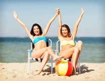 Girls sunbathing on the beach chairs Royalty Free Stock Photo