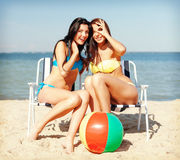 Girls sunbathing on the beach chairs Stock Image