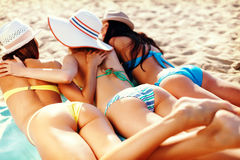 Girls sunbathing on the beach Stock Photo