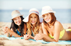 Girls sunbathing on the beach Stock Images