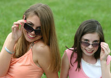 Girls With Sunglasses Close-up. Two girls pulling down sunglasses Stock Photo
