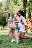Girls in sunglasses holding books and running in park. Multiethnic girls in sunglasses holding books and running in park Royalty Free Stock Image