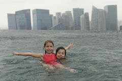 Girls in swimming pool. Two girls having fun in swimming pool on top of  Marina Bay Sands Hotel, with background of skyscrapers Stock Image