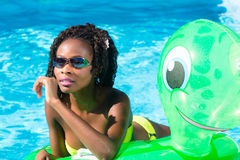 Girls in swimming pool water with inflatable anmimal Stock Image