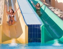 Girls in swimming pool water slide Stock Images