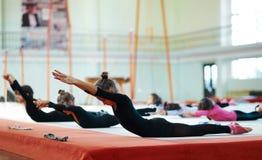 Girls swing back in training  gymnastics Stock Photos