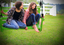 Girls on Swing. Two pretty teenage country girls at play on a swing, both barefooted with long brown hair. Shallow depth of field. Possible flyer or brochure Stock Photo