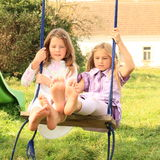 Girls swinging on swing. Two girls - kids playing and swinging on swing royalty free stock photography