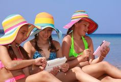 Girls with tablet on the beach Stock Photos