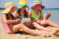 Girls with tablet on the beach Stock Images