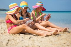 Girls with tablet on the beach Royalty Free Stock Photography