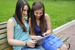 Girls and tablet pc. Two young girls on bench using a tablet computer outdoor in park Royalty Free Stock Photography