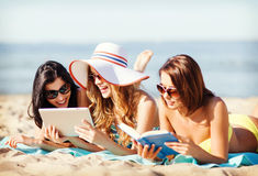 Girls with tablet pc on the beach Stock Photo