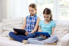 Girls with tablet pc sitting on sofa at home Stock Photography