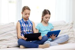Girls with tablet pc sitting on sofa at home Royalty Free Stock Photo