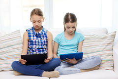 Girls with tablet pc sitting on sofa at home. People, children, technology, friends and friendship concept - girls looking to tablet pc computers at home Stock Photography