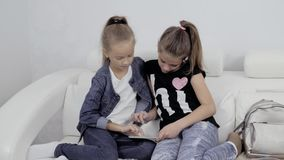 Girls with a tablet. Portrait of two female friends indoors. Two Teenage Girls Looking At Laptop tablet pc. Girls with a tablet. Portrait of two female friends stock footage