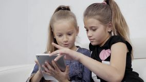 Girls with a tablet. Portrait of two female friends indoors. Two Teenage Girls Looking At Laptop tablet pc. Girls with a tablet. Portrait of two female friends stock video footage