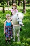 Girls take a walk with pony Stock Photo