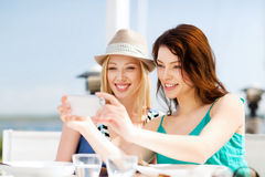 Girls taking photo in cafe on the beach royalty free stock photos