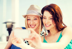 Girls taking photo in cafe on the beach Royalty Free Stock Image