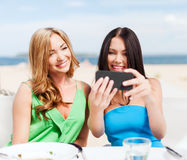 Girls taking photo in cafe on the beach Stock Photography